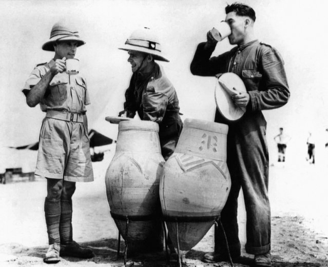 """British soldiers in Egypt drink water from """"Goolahs"""", Clay Containers in which water is cooled by slow evaporation through porous walls, December 14, 1940. (Photo by AP Photo)"""