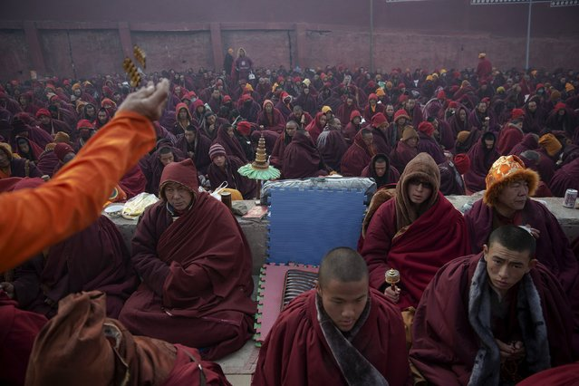 A doctor throws some pills to Tibetan Buddhist monks protecting themselves from cold weather at a Buddhist laymen lodge where thousands of people gather for daily chanting session during the Utmost Bliss Dharma Assembly, the last of the four Dharma assemblies at Larung Wuming Buddhist Institute in remote Sertar county, Garze Tibetan Autonomous Prefecture, Sichuan province, China October 31, 2015. (Photo by Damir Sagolj/Reuters)