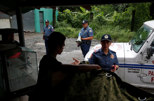 """A police officer talks to a man to ask him to surrender as part of Operation """"Tokhang"""" (Knock and Persuade drug users to surrender) in Magalang, Pampanga in northern Philippines, October 8, 2016. (Photo by Erik De Castro/Reuters)"""
