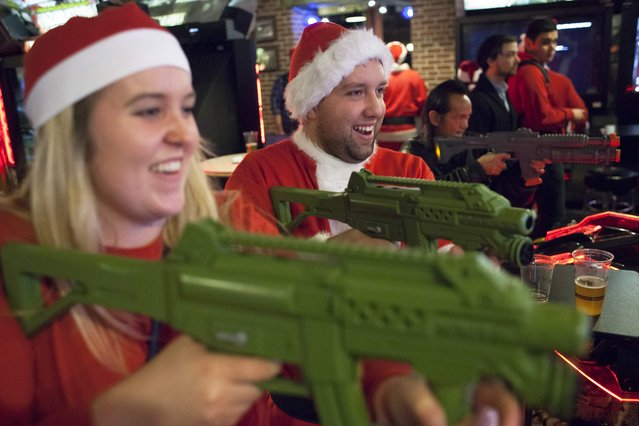 Santarchy participants Victor Celis (R) and Daley Smith (L) play a game at Gameworks in Seattle, Washington December 13, 2014. (Photo by David Ryder/Reuters)