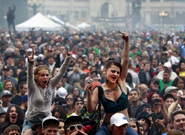Members of a crowd numbering tens of thousands smoke marijuana and listen to live music, at the Denver 420 pro-marijuana rally at Civic Center Park in Denver on Saturday, April 20, 2013. Even before the passage in November 2012 of Colorado Amendment 64 promised the legalization of marijuana for recreational use, April 20th has for years been a celebration of marijuana counterculture, and the 2013 Denver rally draw larger crowds than previous years. (Photo by Brennan Linsley/AP Photo)