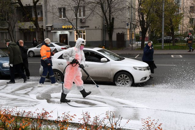 A municipal worker wearing protective equipment sprays disinfectant on a sidewalk in Moscow on November 3, 2020, amid the ongoing coronavirus disease pandemic. (Photo by Natalia Kolesnikova/AFP Photo)