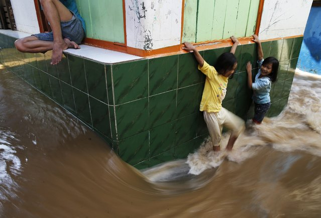 Children try to walk through a flooded street at Kampung Melayu residential area in Jakarta, December 23, 2014. Torrential rains that have continued in Indonesia in recent days have widened the number of flooded areas that include Jakarta and Bandung, a local newspaper said on Tuesday. (Photo by Reuters/Beawiharta)