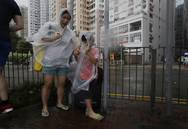 People brave the wind on the waterfront as Typhoon Haima approaches in Hong Kong, Friday, October 21, 2016. Typhoon Haima churned toward southern China on Friday after smashing into the northern Philippines with ferocious wind and rain, triggering flooding, landslides and power outages and killing seven people. (Photo by Kin Cheung/AP Photo)