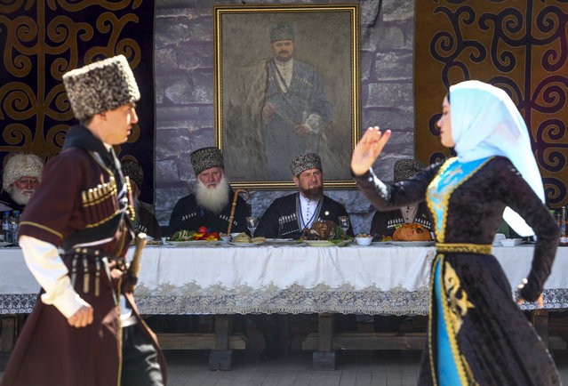 Chechen regional leader Ramzan Kadyrov, background center, dressed in national costume, looks at Chechen dancers during a celebrations of a Day of the Chechen language holiday in Chechnya's provincial capital Grozny, Russia, Wednesday, April 25, 2018. In the back is a portrait of his father Akhmad Kadyrov, the Chechen president who was assassinated in a 2004 bomb blast. (Photo by Musa Sadulayev/AP Photo)