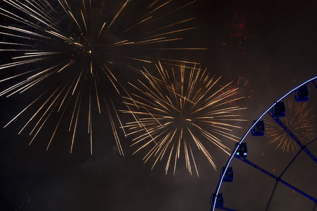 Fireworks explode near the observation wheel during a pyrotechnic show to celebrate the New Year in Hong Kong January 1, 2015. (Photo by Tyrone Siu/Reuters)