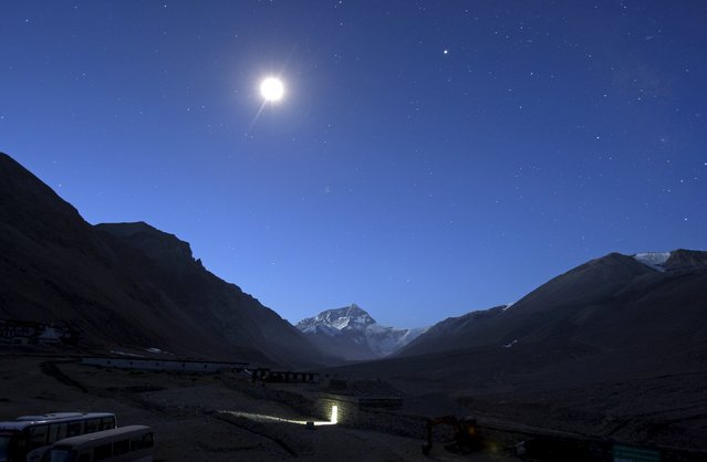 The first light of dawn illuminates Mount Everest as the moon shines above and a toilet block is seen in the foreground in the Tibet Autonomous Region, China, April 29, 2008. (Photo by David Gray/Reuters)
