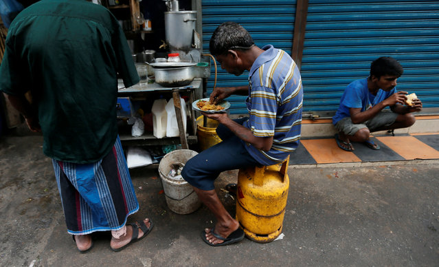 A man sits on a domestic gas tank while having his breakfast at a food stall on a road near a main market in Colombo , Sri Lanka September  30, 2016. (Photo by Dinuka Liyanawatte/Reuters)