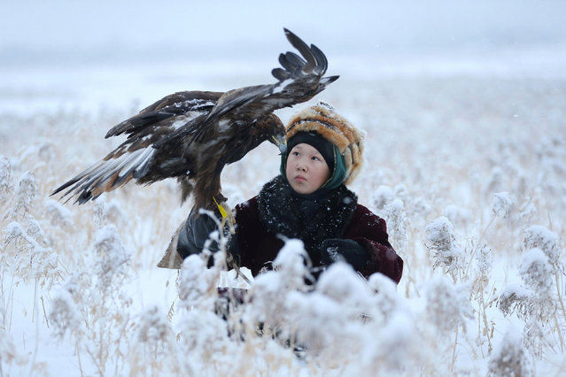 A participant holds his tamed golden eagle during a traditional hunting contest, near the town of Esik in Almaty region, Kazakhstan on December 5, 2020. (Photo by Pavel Mikheyev/Reuters)