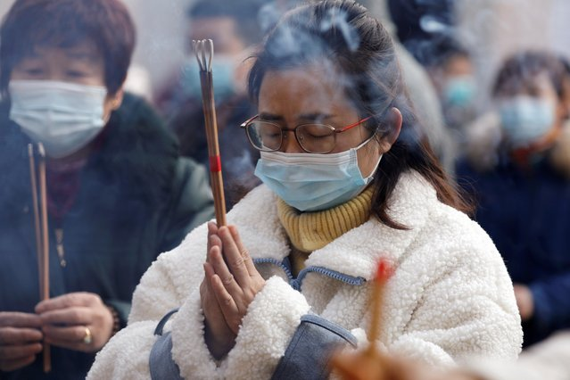 A woman wearing protective face mask prays at a Buddhist temple on New Year's Day, in Wuhan, Hubei province, China January 1, 2021. (Photo by Tingshu Wang/Reuters)