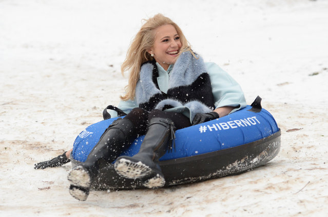 Singer Pixie Lott sledges down a hill covered with artificial snow at Alexandra Palace in London, as part of a pop-up winter wonderland created for local visitors, Saturday January 10, 2015. (Photo by Stefan Rousseau/AP Photo/PA Wire)