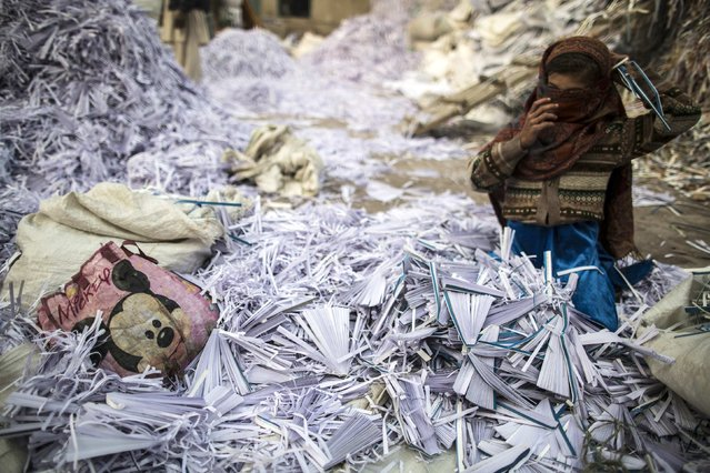 Razia, 9, fixes her scarf as she sorts papers before they are taken to a factory to be recycled in Lahore January 12, 2015. (Photo by Zohra Bensemra/Reuters)