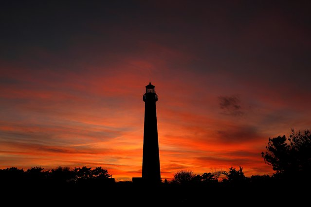 The sun sets behind the Cape May Lighthouse in Cape May, New Jersey, U.S., December 13, 2020. (Photo by Mike Segar/Reuters)
