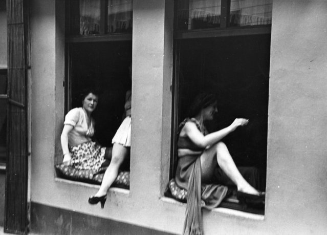 Licensed street prostitutes barter with customers through the windows of their brothels in Hamburg.  Original Publication: Picture Post - 4854 - The Two Germanys - A Warning - pub. 1949   (Photo by Bert Hardy/Getty Images)