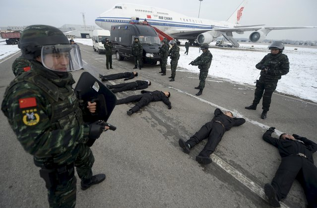 Armed paramilitary policemen guard as mock hijackers lie on the ground near a passenger jet during an anti-terrorism drill on plane hijacking, at the Beijing Capital International Airport, in Beijing, China, December 3, 2015. (Photo by Reuters/Stringer)