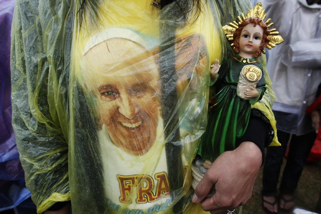A Catholic faithful holds a statue of child Jesus during an open-air Mass led by Pope Francis at Rizal Park in Manila January 18, 2015. (Photo by Cheryl Ravelo/Reuters)