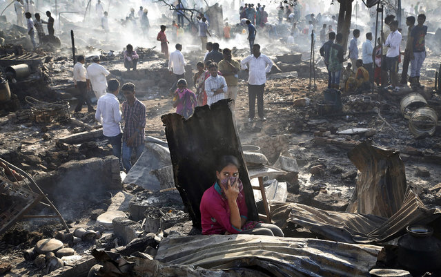 People look at the devastation caused by fire that broke out at slums in Kadivali area of Mumbai, India, Monday, December 7, 2015. Hundreds of homes were reportedly destroyed as fire tenders labored to reach the source in the heavily congested area. (Photo by Rajanish Kakade/AP Photo)