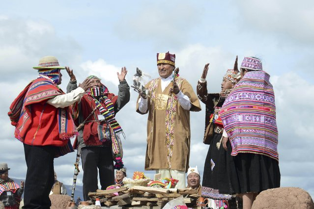 Bolivia's President Evo Morales (C) wears ceremonial clothes as he participates in a ceremony in Tiahuanaco, some 70 km from La Paz, in this January 21, 2015 handout photo provided by the Bolivian Presidency. (Photo by Reuters/ABI/Bolivian Presidency)