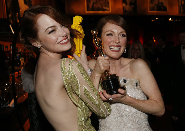 """Emma Stone compares her Lego Oscar statuette with actress Julianne Moore's genuine Oscar for best leading actress for her role in """"Still Alice"""" at the Governors Ball following the 87th Academy Awards in Hollywood, February 22, 2015. (Photo by Mario Anzuoni/Reuters)"""