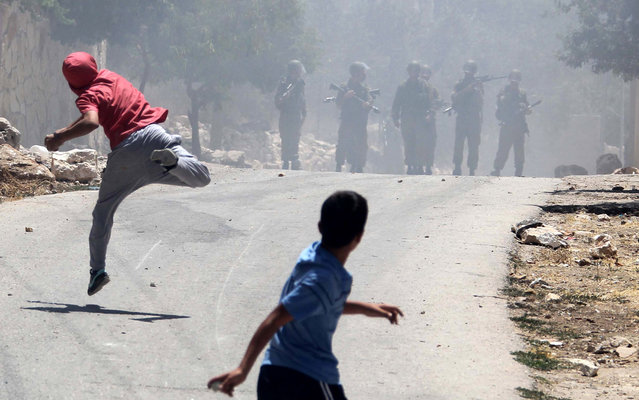 Palestinian protesters throw stones towards Israeli security forces during clashes following a protest against the expropriation of Palestinian land by Israel in the village of Kfar Qaddum near the occupied West Bank city of Nablus on June 28, 2013. (Photo by Jaafar Ashtiyeh/AFP Photo)