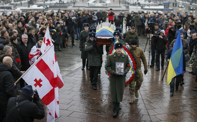 "Ukrainian soldiers carry the coffin bearing the body of Georgian Tomaz Sukhiashvili, 35, a member of the self-defence battalion ""Donbass"", who was killed in the fighting in eastern Ukraine, during a funeral ceremony at Independence Square in central Kiev January 21, 2015. (Photo by Gleb Garanich/Reuters)"