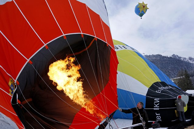 A pilot inflates his balloon before the 37th International Hot Air Balloon Week in Chateau-d'Oex, January 24, 2015. According to the organizers, over 80 balloons from 20 countries are participating in the ballooning event in the Swiss mountain resort. (Photo by Pierre Albouy/Reuters)