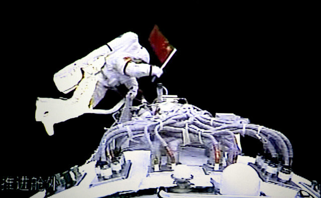 In this video grab taken at the Beijing Space Command and Control Center released by China's Xinhua News Agency, Saturday, September 27, 2008, Chinese astronaut Zhai Zhigang steps outside the orbit module of the Shenzhou-7 spacecraft for a spacewalk. (Photo by AP Photo/Xinhua via The Atlantic)