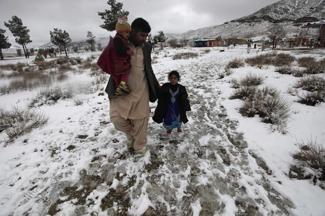 A man and his daughters walk along the snow-covered Hanna Lake after a snowfall on the outskirts of Quetta January 21, 2015. (Photo by Naseer Ahmed/Reuters)