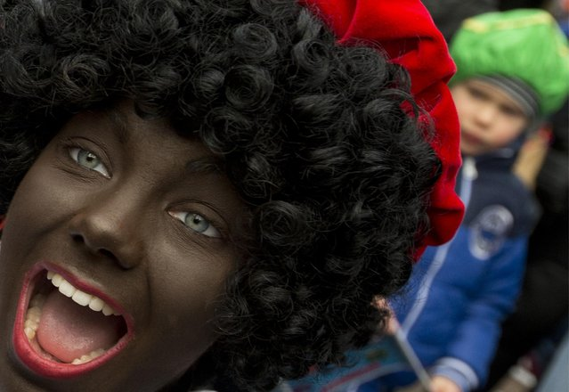 A Black Pete interacts with children during the arrival of Sinterklaas, or Saint Nicholas, in Maassluis, Netherlands, Saturday, November 12, 2016. Sinterklaas and his helper Black Pete are at the center of a long-time controversy because Pete is often played by white people in blackface makeup. (Photo by Peter Dejong/AP Photo)