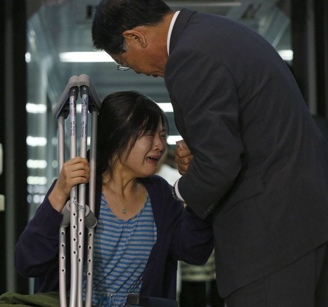 Kim Yoon-ju (L), a flight attendant who was on Asiana Airlines flight 214 which crashed in San Francisco, cries as she is greeted by Park Sam-koo, chairman of the Kumho-Asiana group, as she arrives at the Incheon Airport in Incheon, west of Seoul July 11, 2013. Asiana Airlines Flight 214 crashed in San Francisco on Saturday, killing two teenage girls and injuring more than 180 people. (Photo by Kim Hong-Ji/Reuters)