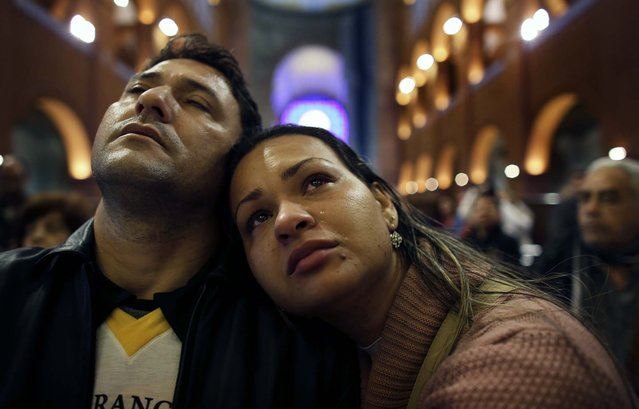 A pilgrim cries next to her husband as they pray inside the Basilica of Our Lady of Aparecida, Brazil's patron saint, in the city of Aparecida Do Norte, 103 miles east of Sao Paulo on July 23, the day before Pope Francis's visit to the basilica. (Photo by Nacho Doce/Reuters)