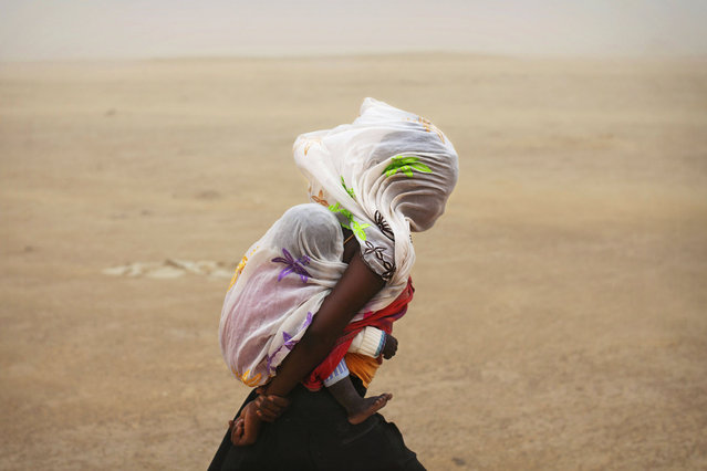 A woman carrying her baby and wrapped with a shawl walks through a sandstorm in Timbuktu July 29, 2013. (Photo by Joe Penney/Reuters)
