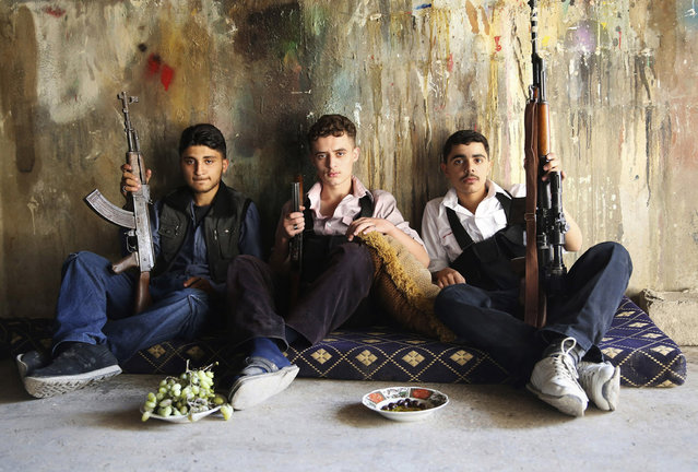 """Free Syrian Army"" fighters hold their weapons as they pose for a picture in Jobar, Damascus. (Photo by Mohamed Abdullah/Reuters)"