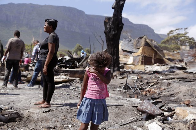 A young girl covers her face as dust blows, close to the remains of her family home that burnt down after a fire spread through a township, near Hout Bay on the outskirts of  Cape Town, South Africa, Monday, December 28, 2015. A fire department spokesman says nine people were killed in fires in the South African city of Cape Town over the weekend. On Monday, Fire and Rescue Services spokesman Theo Layne said about 1,500 people were left homeless over the holiday weekend as five separate fires blazed in the coastal city.  (Photo by Schalk van Zuydam/AP Photo)