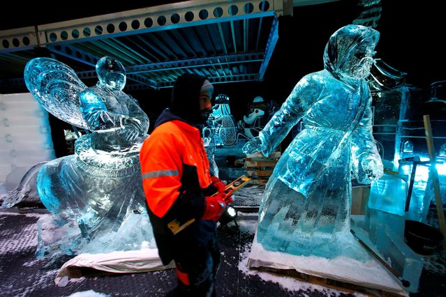 "A sculptor walks past ice sculptures at the Snow and Ice Sculpture Festival ""Eiswelt Mainz"" in Mainz, Germany, November 22, 2016. (Photo by Ralph Orlowski/Reuters)"