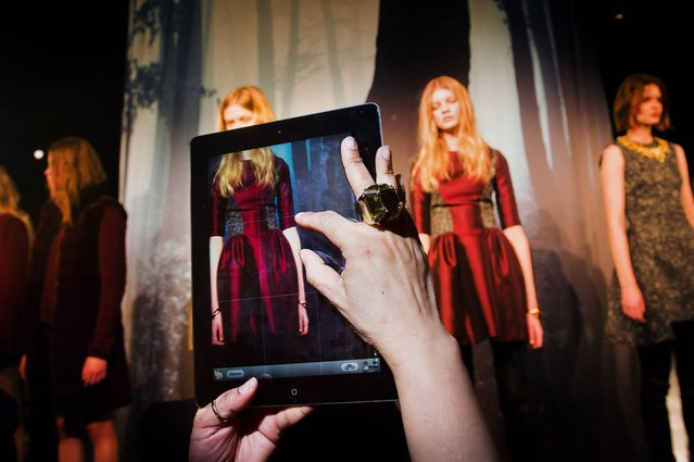 """A guest takes an iPad photo of the models during the ADEAM presentation at Lincoln Center. Mercedes-Benz Fashion Week, New York City, Fall 2013. From the series """"Fashion Lust"""". (Photo by Dina Litovsky)"""