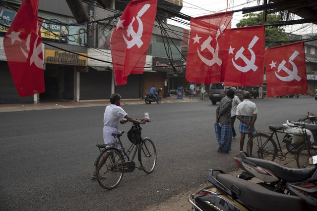 A man pushes his bicycle past Communist Party of India (Marxist) flags displayed as part of election campaign in Kochi, Kerala state, India, Thursday, March 25, 2021. The southern state goes to polls on April 6 to elect members to its state legislature. (Photo by R.S. Iyer/AP Photo)