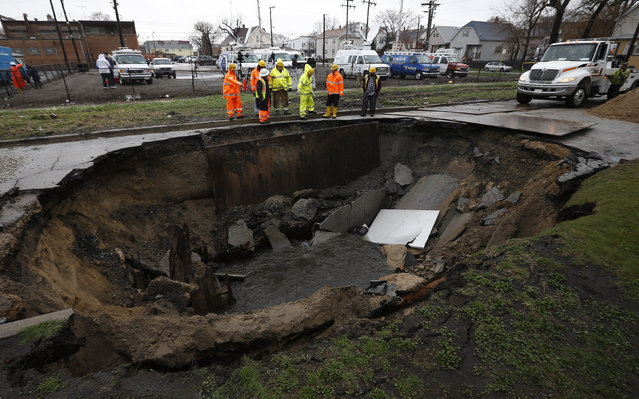 Workers look into a sinkhole caused by a broken water main in Chicago, Illinois, April 18, 2013. Heavy rains and flooding brought havoc to the Chicago area on Thursday, shutting major expressways, delaying commuter trains for hours, cancelling flights, flooding basements and closing dozens of suburban schools. On the city's South Side, a sinkhole opened up on a residential street, swallowing three cars, according to Officer Mike Sullivan of the Chicago Police Department. One person was hospitalized with non-life-threatening injuries. (Photo by Jim Young/Reuters)