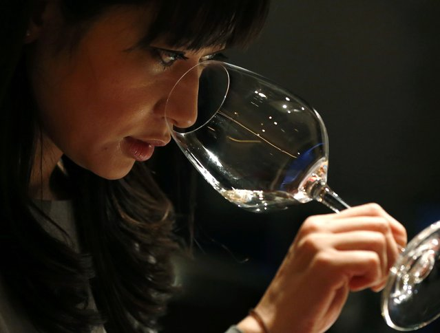 "Ayana Misawa, chief winemaker of Grace Wine, smells a glass of wine at a restaurant in Tokyo January 17, 2015. Making wine comes naturally to Misawa, having spent her childhood in vineyards watching her father and grandfather nurture cherished ""koshu"" grapes, a unique Japanese variety known for its fresh and fruity overtones. Misawa and other winemakers in the wine hub of Yamanashi Prefecture are set on matching the success of Japan's automakers and whisky distillers, which have taken the world by storm. (Photo by Toru Hanai/Reuters)"