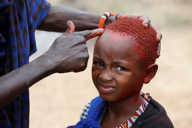 A Maasai boy is painted with red ochre pigment during an initiation into an age group ceremony near the town of Bisil, Kajiado county, Kenya on August 23, 2018. (Photo by Baz Ratner/Reuters)