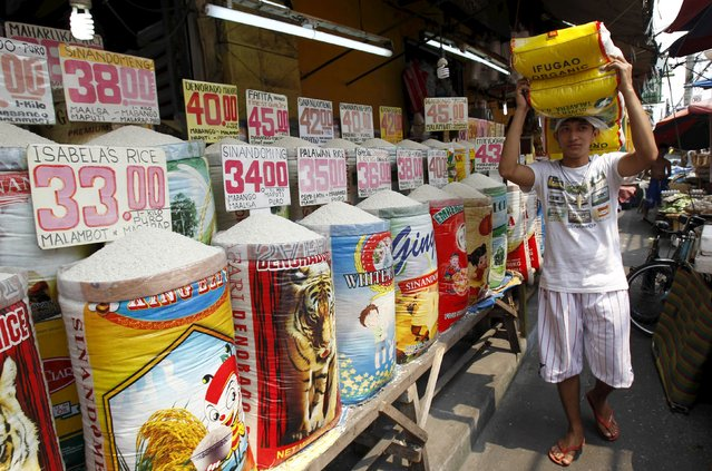 A worker walks past various brands of rice for sale, while carrying sacks of rice on his head, at a market in Manila in this March 5, 2014 file photo. Philippine annual inflation picked up more than expected in December to hit its highest in seven months, the statistics agency said on January 5, 2016, reflecting increases in food, alcoholic drinks and tobacco, healthcare, transport and recreation costs. (Photo by Romeo Ranoco/Reuters)
