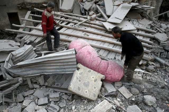 Residents remove a mattress from under debris in a site hit by what activists said were airstrikes carried out by the Russian air force in the town of Douma, eastern Ghouta in Damascus, Syria January 10, 2016. (Photo by Bassam Khabieh/Reuters)