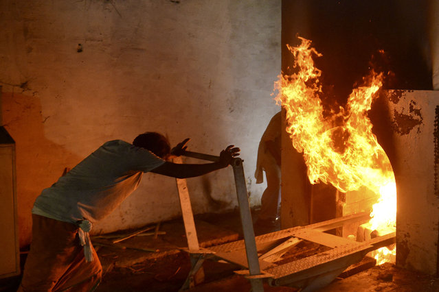 A worker pushes a trolley that carried the body of patient who died of the Covid-19 coronavirus into an furnace during the cremation at an electric crematorium in Allahabad on April 27, 2021. (Photo by Sanjay Kanojia/AFP Photo)