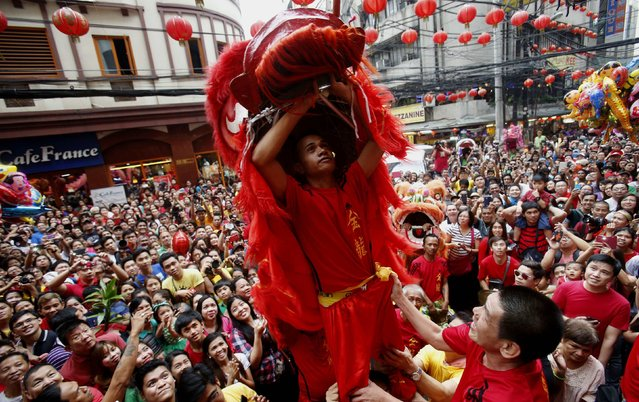 "A lion dance performer waits for ""Ang Pao"", or a money gift, in front of a grocery next to revellers as they celebrate Lunar New Year at Manila's Chinatown February 19, 2015. (Photo by Erik De Castro/Reuters)"