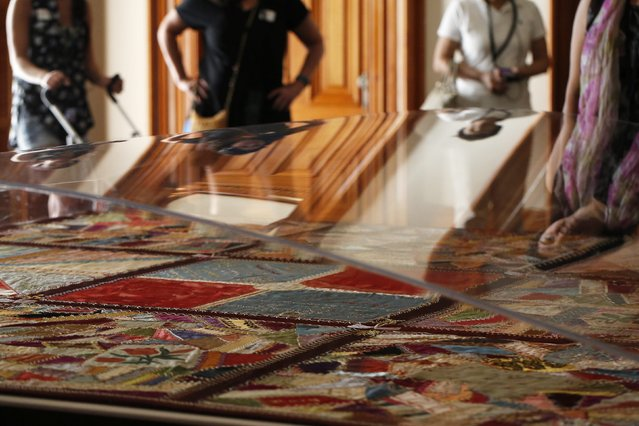 Visitors look at a handmade quilt by deposed Hawaiian Queen Lili'uokalani in her 1895 captivity in the Iolani Palace, now a museum in Honolulu, Hawaii December 22, 2015. (Photo by Jonathan Ernst/Reuters)