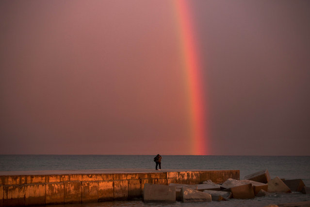 A couple kiss each other as a rainbow forms just after a storm at a breakwater facing the Mediterranean Sea in Barcelona, Spain, Wednesday, February 4, 2015. (Photo by Emilio Morenatti/AP Photo)