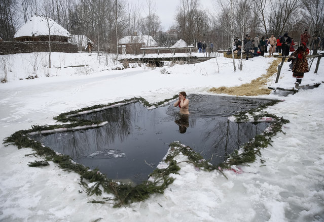 A woman reacts as she takes a dip in a lake during Orthodox Epiphany celebrations in Kiev, Ukraine, January 19, 2016. (Photo by Gleb Garanich/Reuters)