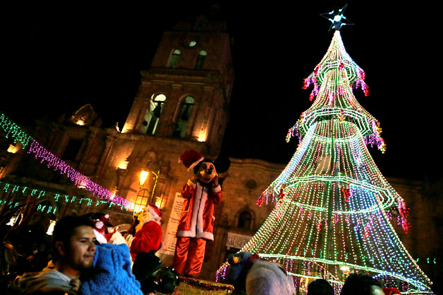 Residents look at a Christmas tree in San Francisco square, La Paz, Bolivia, December 10, 2016. (Photo by David Mercado/Reuters)