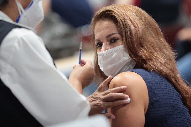 A nurse shows a syringe with a dose of the COVID-19 vaccine to a citizen who is about to receive it during a vaccination day as part of the campaign in Mexico City at Pepsi Center WTC on May 25, 2021 in Mexico City, Mexico. According to the head of Govermnment, Claudia Sheinbaum, seven municipalities will start their campaign today which plans to apply the first dose to over 500,000 citizens between 50 and 59 years old. (Photo by Hector Vivas/Getty Images)