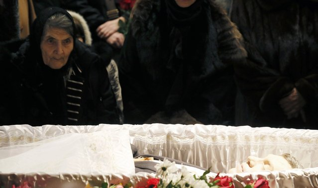 Dina Eidman (L), mother of Russian leading opposition figure Boris Nemtsov, looks on near the coffin during a memorial service before the funeral of Nemtsov in Moscow, March 3, 2015. Several hundred Russians, many carrying red carnations, queued on Tuesday to pay their respects to Nemtsov, the Kremlin critic whose murder last week showed the hazards of speaking out against Russian President Vladimir Putin. REUTERS/Maxim Shemetov